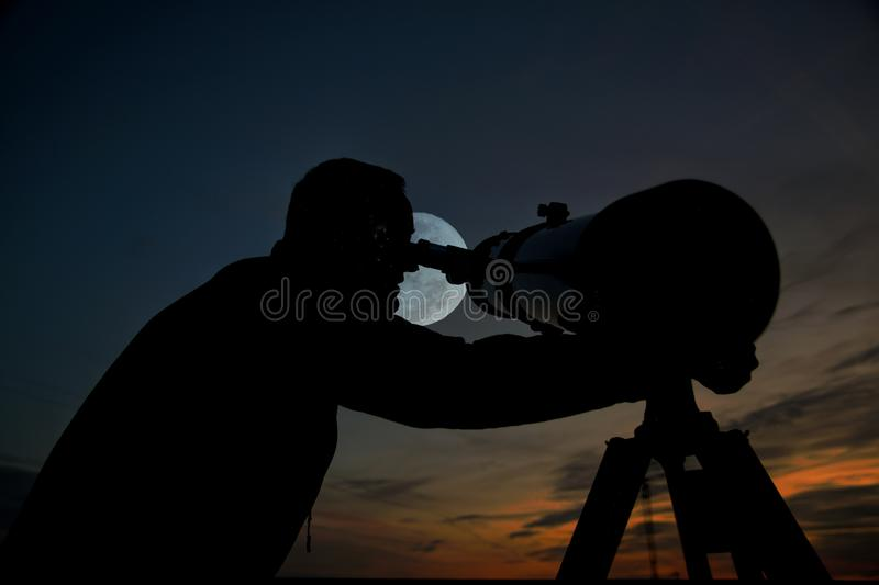 Adult man using a telescope at sunset time observing the moon at night. Amateur astronomy concept with empty copy space royalty free stock photos