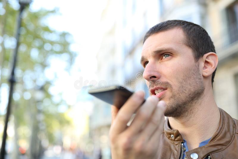 Adult man using voice recognition on phone to send a message royalty free stock image