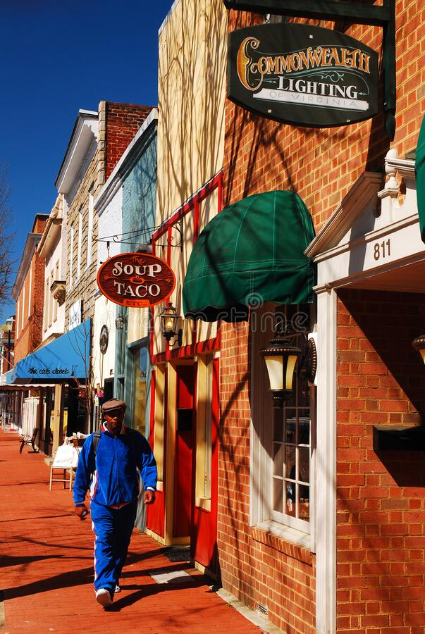Walking in charming downtown Fredericksburg, Virginia. An adult man walks past the cute boutiques in charming downtown Fredericksburg, Virginia royalty free stock photography