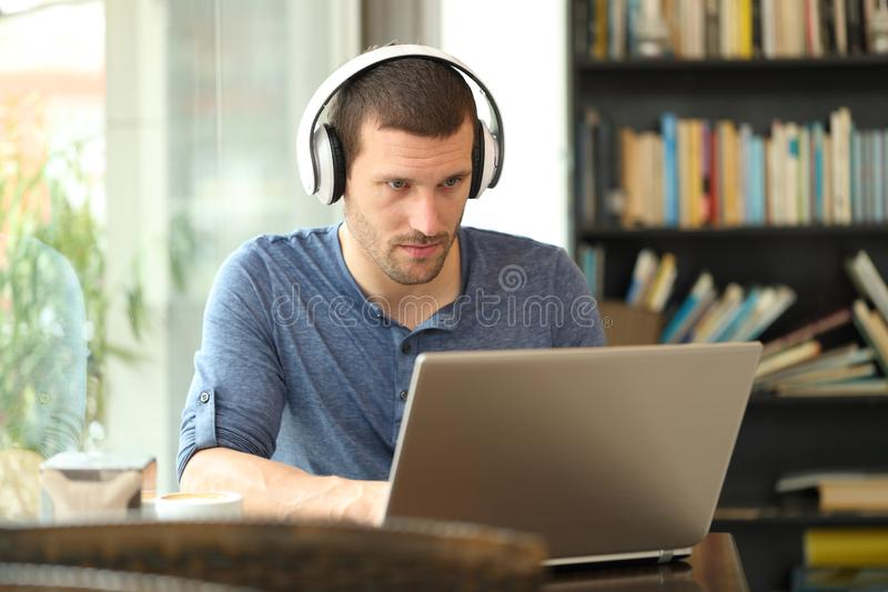 Adult man wearing headphones using a laptop. E-learning in a coffee shop or home royalty free stock photography