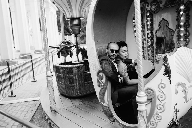 Adult man and woman on a carousel. Adult men and women on merry go round carousel royalty free stock photos