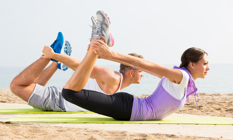 Download Adult Man And Woman Training On Beach By Sea Stock Photo - Image: 83702460