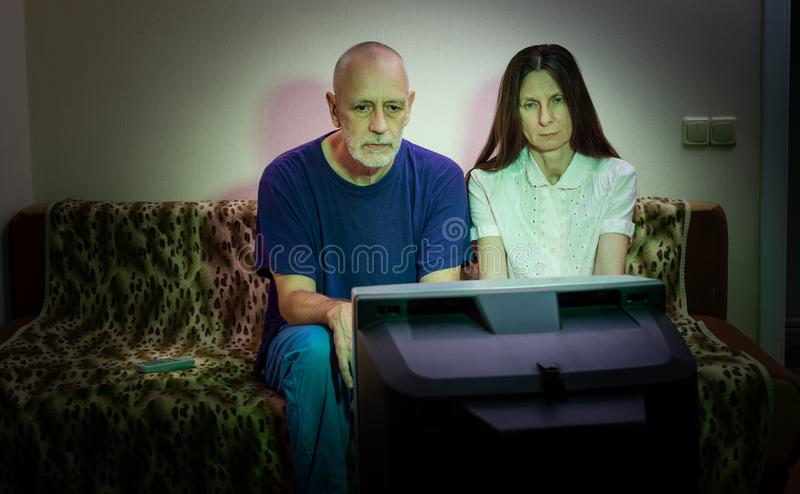 Adult man and woman, watch television, looking sad, sitting on a couch stock image