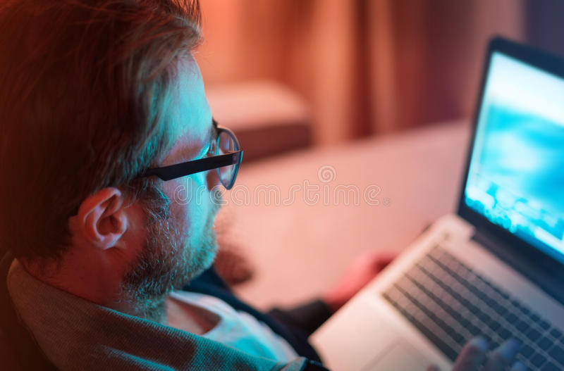 Adult man working by night on laptop computer at home stock images