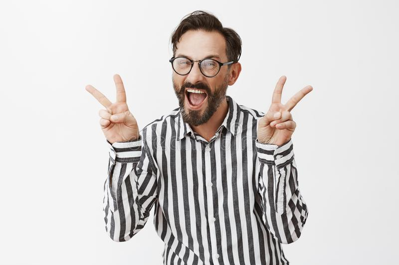 Adult mature guy never hide he is anime fan. Joyful carefree immature male model with beard in striped shirt, showing royalty free stock photos