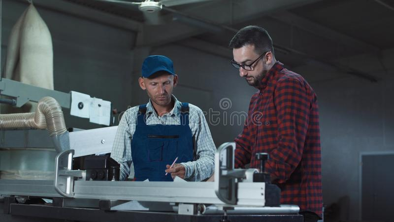 Men with papers in joinery. Adult men standing in joinery shop and coworking with blueprints royalty free stock photo