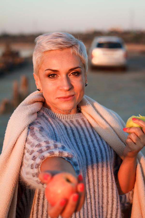Adult middle-aged blonde woman in a sweater eating an apple and holding out another one to the camera, selective focus royalty free stock photos