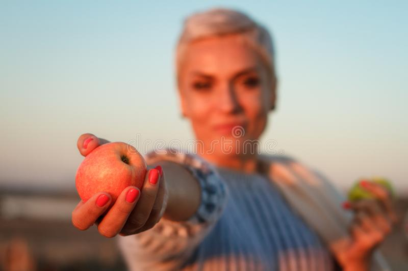 Adult middle-aged blonde woman in a sweater eating an apple and holding out another one to the camera, selective focus royalty free stock photo