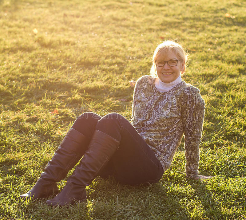 Adult, nice woman sitting on grass meadow. Soft focus stock photo