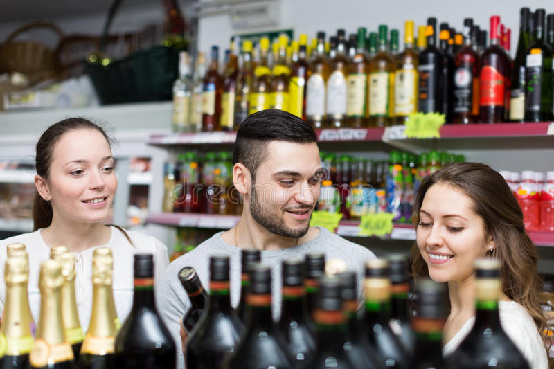 Adult people choosing liquors. Adult people choosing alcoholic beverages in a liquor store royalty free stock photography