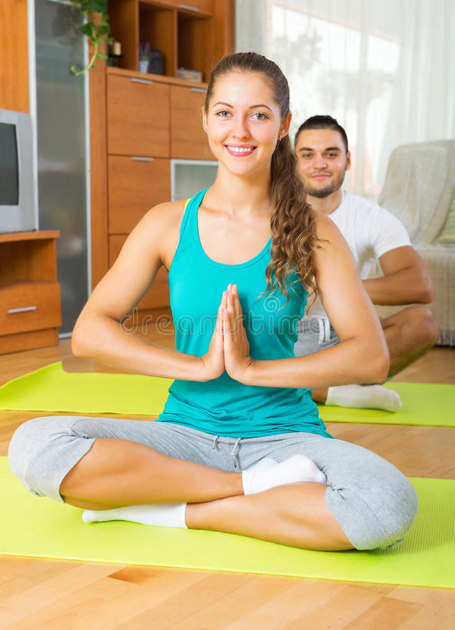 Adult people doing yoga indoor. Adult smiling people doing yoga on mats in interior royalty free stock photo