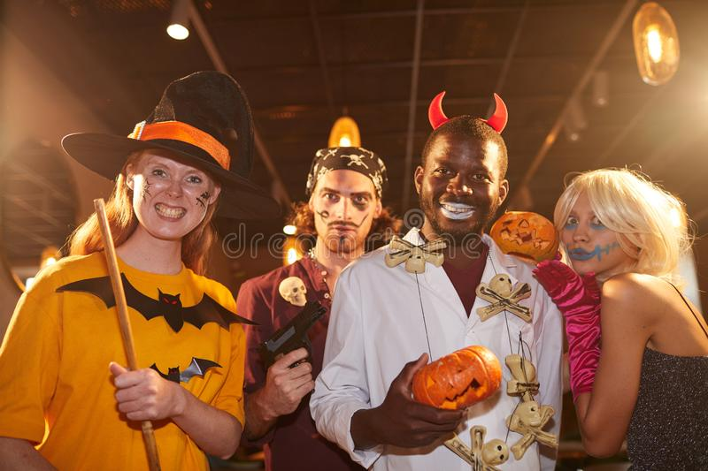 Adult People wearing Halloween Costumes. Waist up portrait of adult people wearing Halloween costumes posing as witches and pirates grimacing at camera during stock image