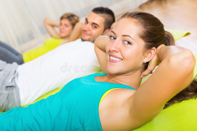 Adult people working in gym. Adult active people working out on mats in gym stock images