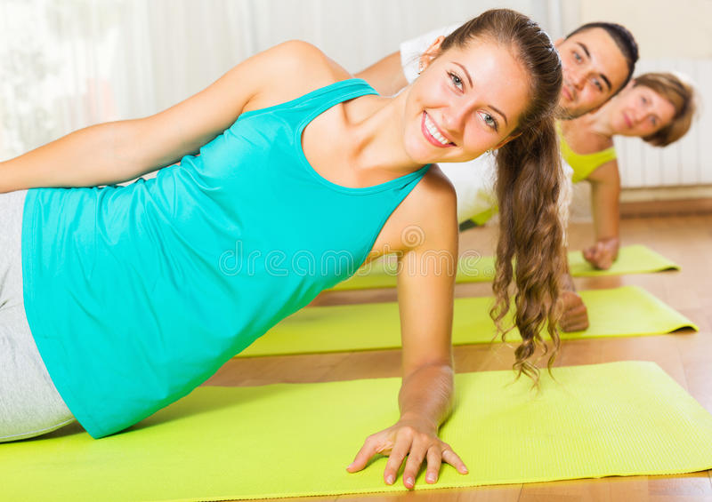 Adult people working in gym. Adult positive people working out on mats in gym stock photos