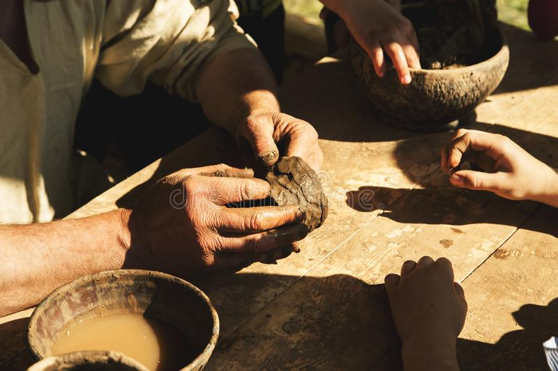 Adult person teaching young people how work with raw clay. Art, craft, creativity, finger, form, hand, making, pottery, traditional, brown, ceramic, creation royalty free stock images
