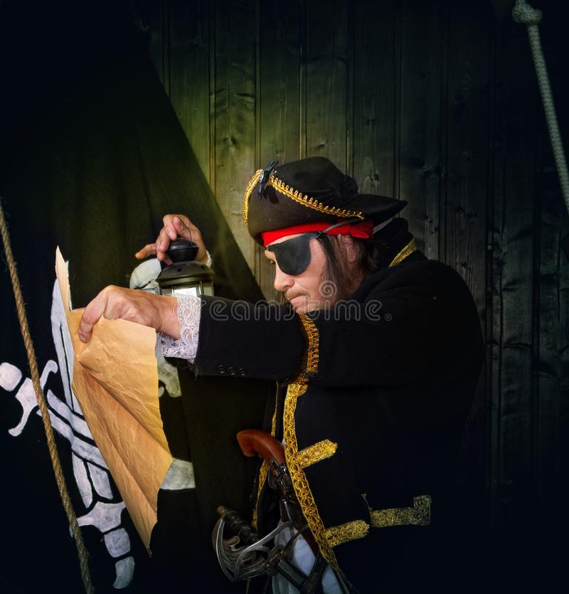 Mature Pirate Capitan. Adult pirate captain in a traditional costume and with arms looks at a treasure map against the backdrop of a jolly roger stock images