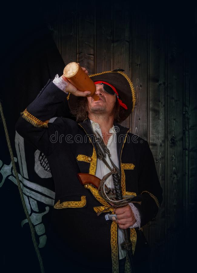 Mature Pirate Capitan. Adult pirate captain in a traditional costume and with weapons drinks rum from a clay bottle against the background of a jolly roger royalty free stock photos