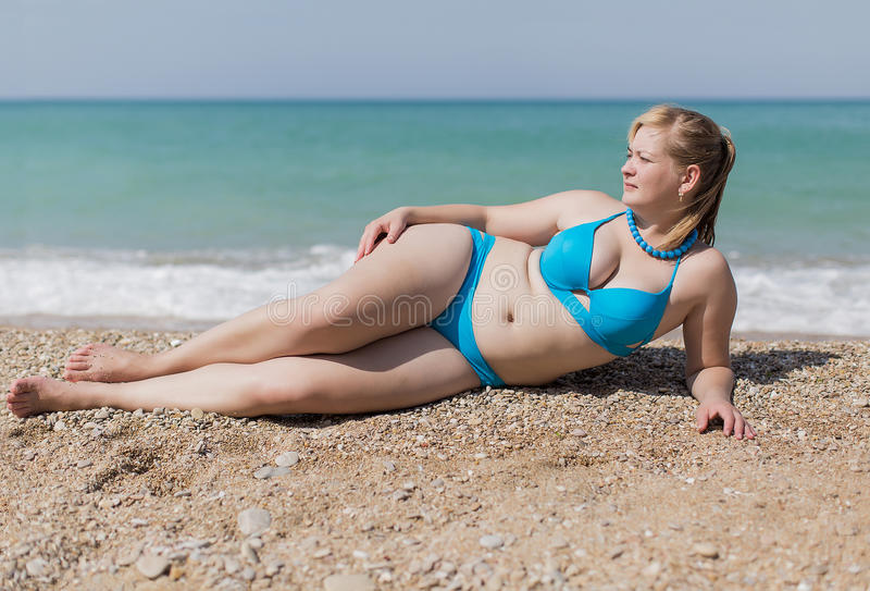 Adult plump woman in blue bikini lying on pebble stock image