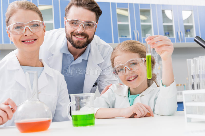 Adult scientists and little girl in goggles with tubes royalty free stock image