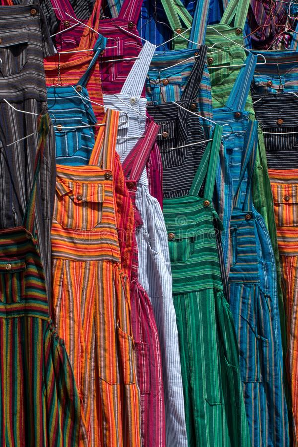 Adult sized coveralls. Hanging at a vendor`s stall in the artisan`s market in Otavalo, Ecuador stock image