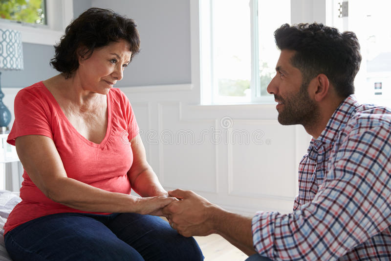 Adult Son Comforting Mother Suffering With Dementia stock image