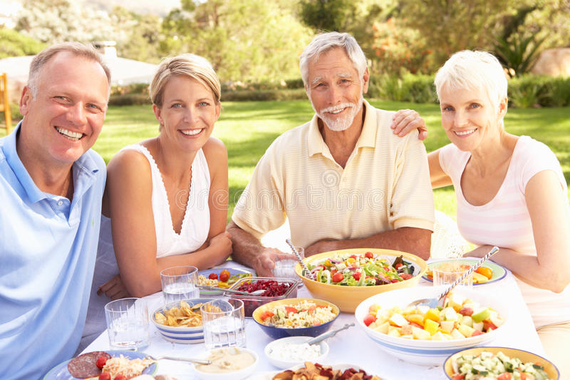 Adult Son And Daughter Enjoying Meal In Garden stock images