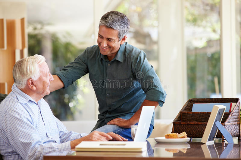 Adult Son Helping Father With Laptop. At Home Putting Hand On Shoulder Smiling royalty free stock image