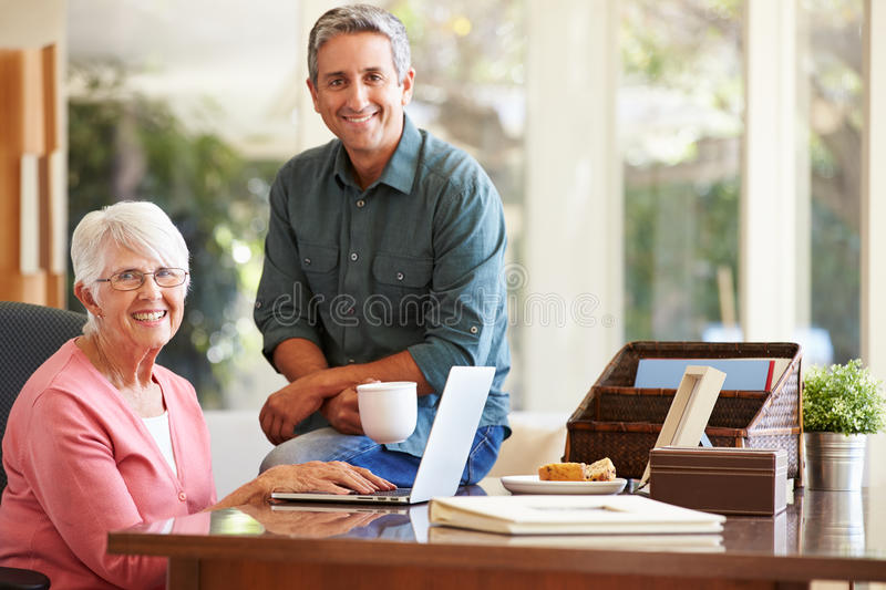 Adult Son Helping Mother With Laptop. Holding Hot Drink Smiling At Camera royalty free stock images