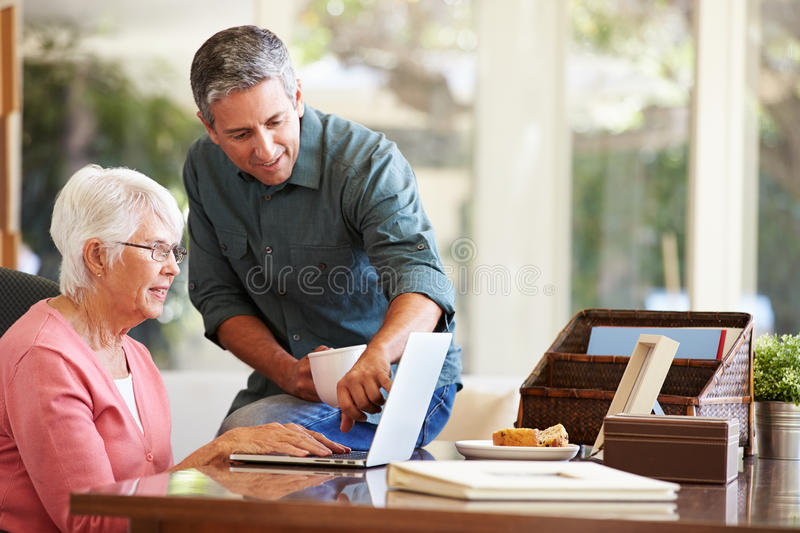 Adult Son Helping Mother With Laptop. Holding Hot Drink Whilst Pointing At Screen stock images