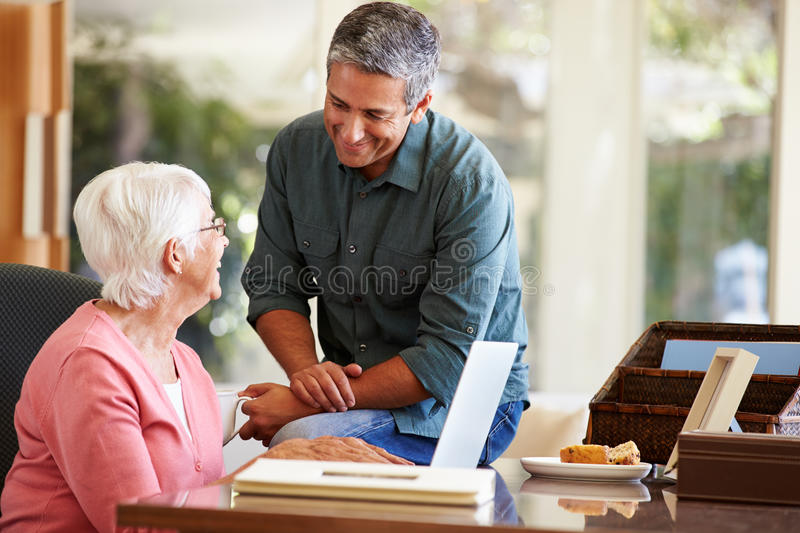 Adult Son Helping Mother With Laptop. At Home Smiling At Each Other stock photography