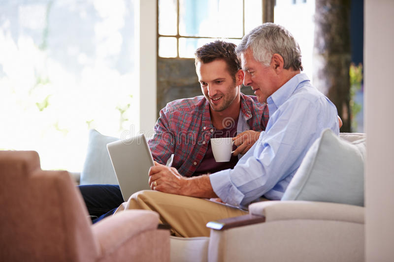 Adult Son Helping Senior Father With Computer At Home stock photography