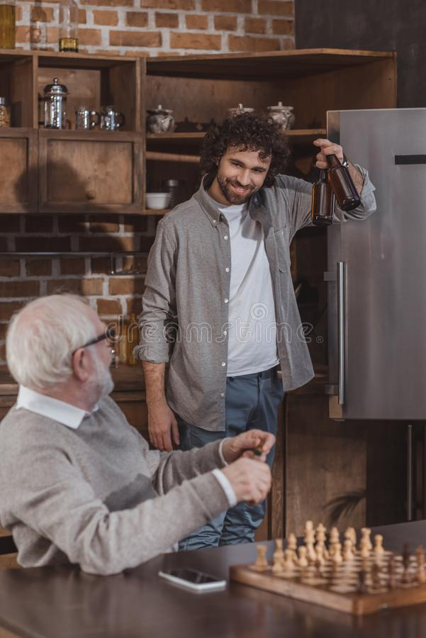 Adult son proposing beer to senior father. At home royalty free stock images