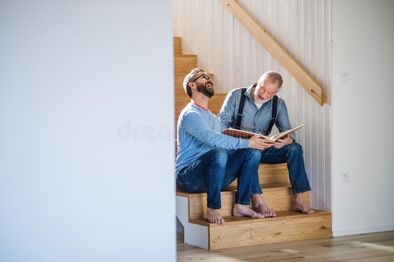 An adult son and senior father sitting on stairs indoors at home, looking at photographs. royalty free stock photography