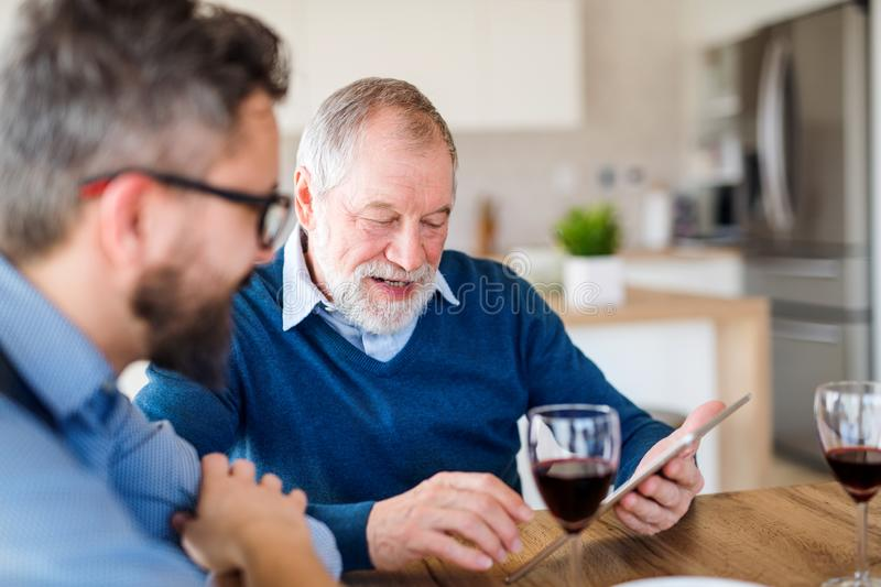 Adult son and senior father sitting at the table indoors at home, using tablet. stock photo