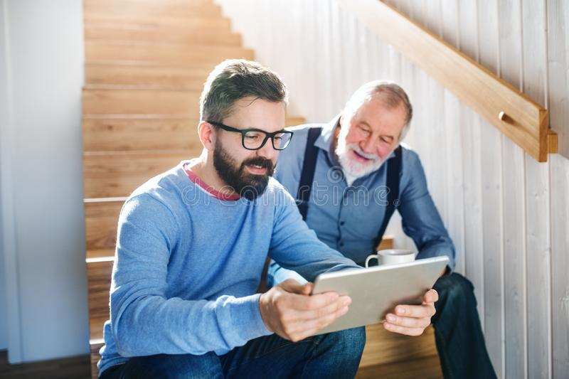 An adult son and senior father with tablet sitting on stairs indoors at home. stock images