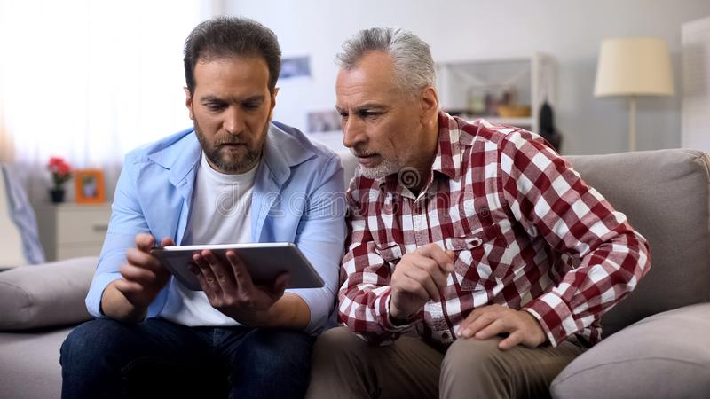 Adult son and senior father watching tutorial videos on tablet, information. Stock photo royalty free stock photo