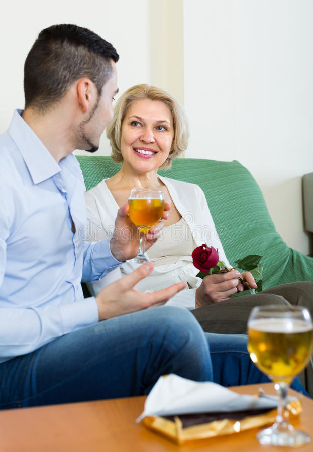 Adult son and senior mother with wine. Adult son congratulating happy smiling mother and proposing a toast royalty free stock images