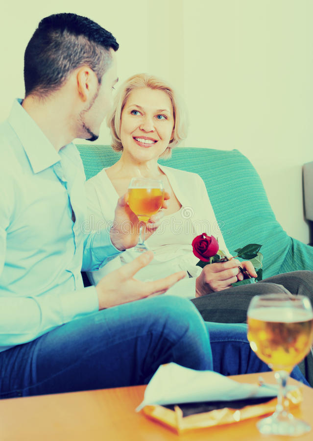 Adult son and senior mother with wine. Adult son congratulating happy smiling mother and proposing a toast royalty free stock photo