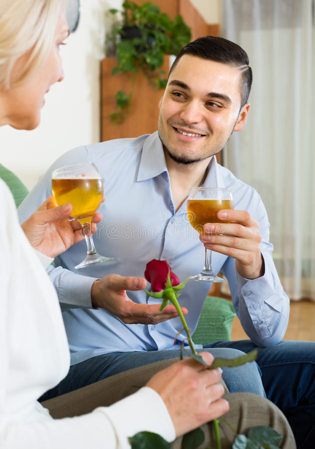 Adult son and senior mother with wine. Smiling adult son congratulating senior mother and proposing a toast royalty free stock photos