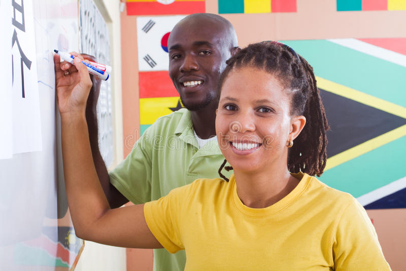 Adult students learning chinese writing. Two african american adult students learning chinese writing royalty free stock photography