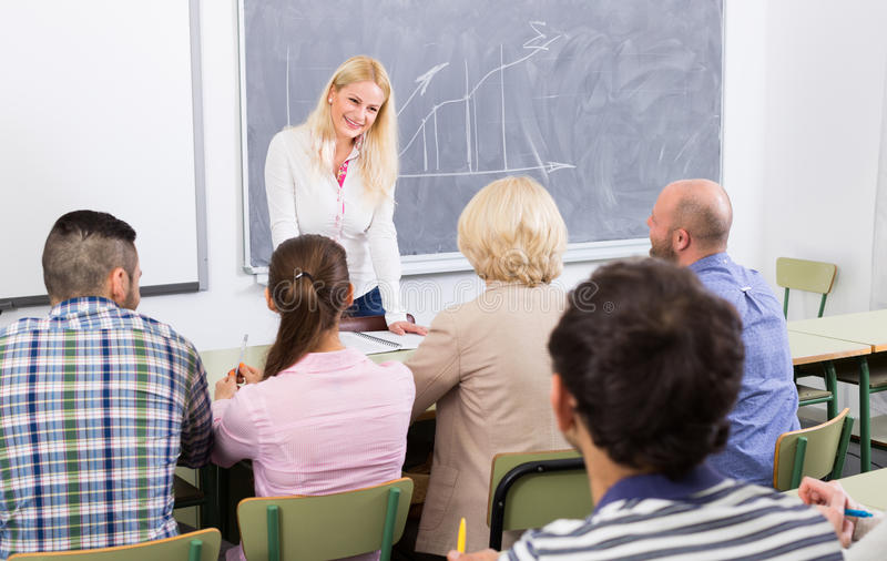 Adult students with teacher in classroom stock image