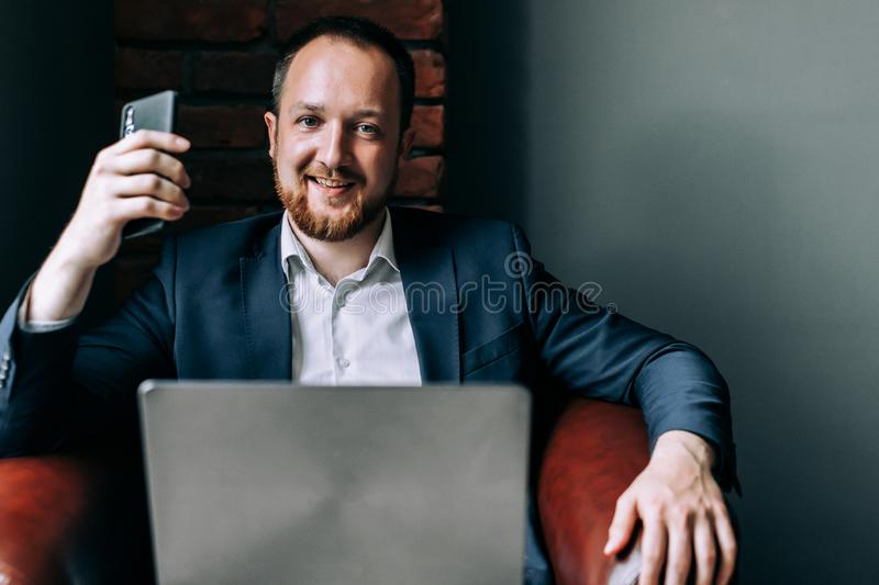 Successful Businessman in suit sitting in a chair with a laptop, holding a smartphone in his hand and smiling stock image