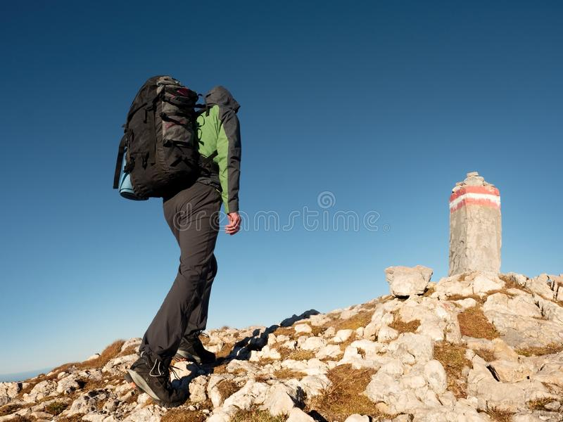 Adult tourist with backpack walk on mountain peak. Last step to summit stone. On mountain top. Tourist walk with heavy backpack royalty free stock images