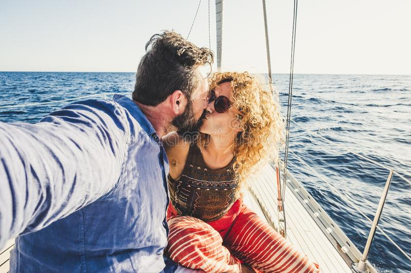 Adult traveler couple in love on a sail boat - people enjoying the summer holiday vacation doing a trip - outdoor leisure activity. Alternative lifestyle men stock photo