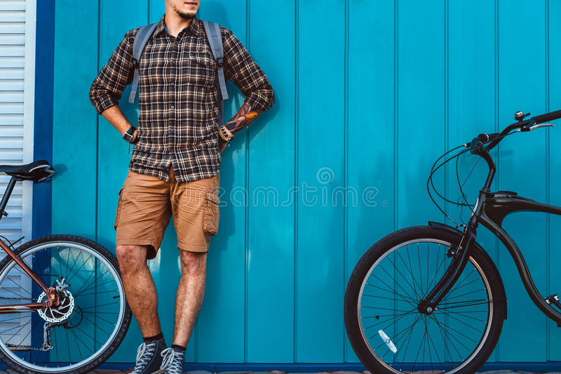 Adult Traveler Man Stands With A Bicycles Near Blue Wall Daily Lifestyle Urban Resting Concept. Unrecognizable young man traveler with a backpack stands next to royalty free stock images