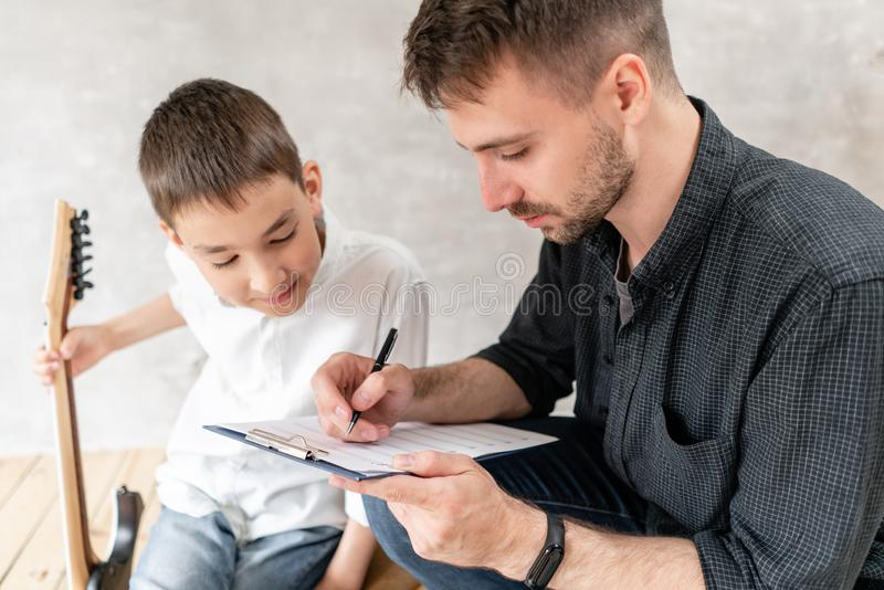 Adult tutor wit his young student prepare to new music lesson with electric guitar royalty free stock photos