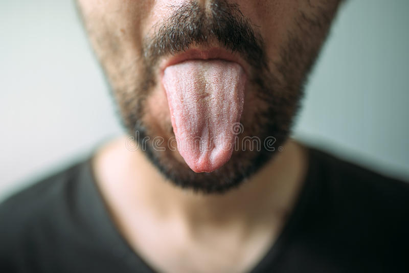 Adult unshaven man sticking tongue out. Selective focus stock image