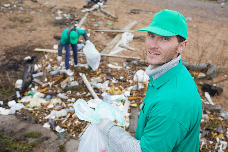 Adult activist looking at camera. Adult volunteer with rubbish bag looking at camera and standing at litter pile royalty free stock photography