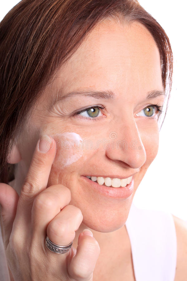 Adult woman applies cream on face stock photo