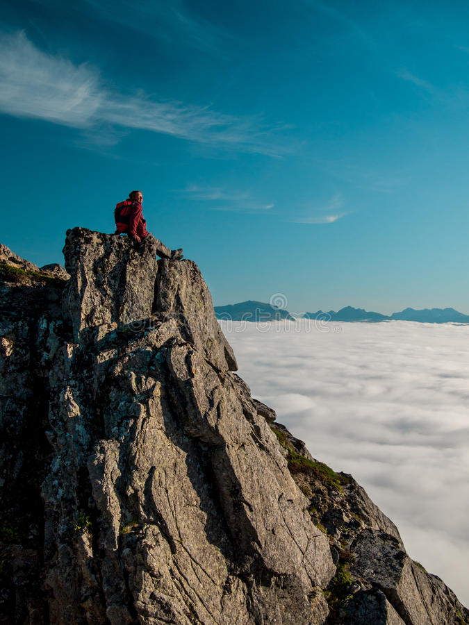 Adult woman with a backpack resting on the edge of a cliff and looking at the sunrise against the blue sky. And thick clouds floating down stock photos
